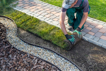 Photo sur Aluminium Jardin Landscape Gardener Laying Turf For New Lawn