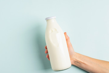 Female hand holds milk or white milk drink in a glass bottle on white background. Healthy eating concept. Flat layout .