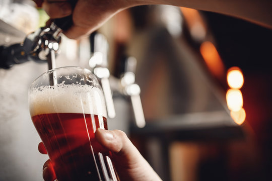 Bartender pours craft drink beer from tap into glass, dark background