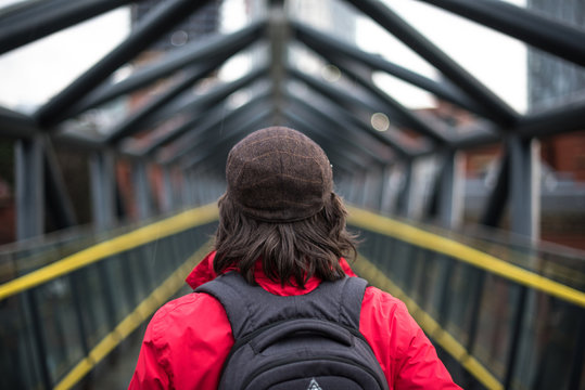 Back of tourist girl with backpack travels through city, against the background of urban bridge yellow lines symmetry explorer hike travel