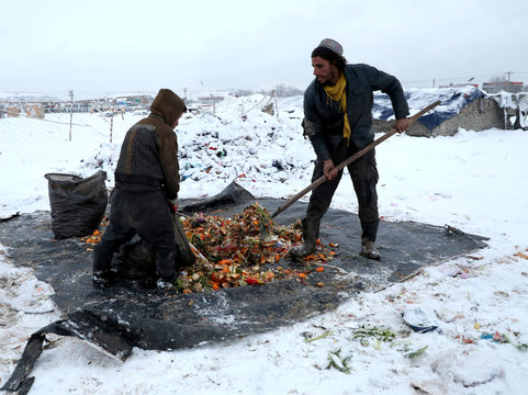 Afghan men upload recycle items on sacks during a snowfall in Kabul