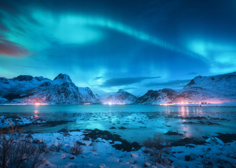 Photo sur Toile Aurore polaire Aurora borealis over the sea coast, snowy mountains and city lights at night. Northern lights in Lofoten islands, Norway. Starry sky with polar lights. Winter landscape with aurora reflected in water