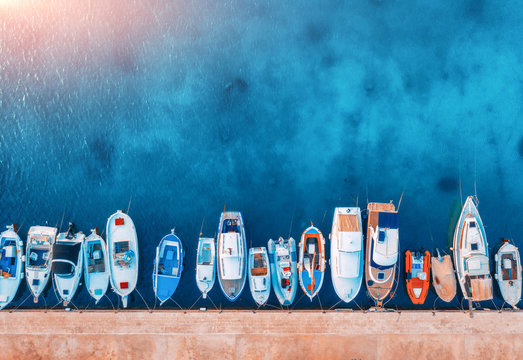 Aerial view of the boats and yachts on tropical sea coast at sunset in summer. Colorful landscape with pier, boat, ocean with transparent blue water. Top view of motorboats in harbor. Travel