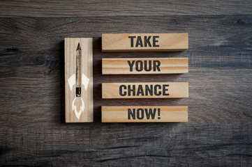 Wooden pieces on a wooden background with message Take your chance now