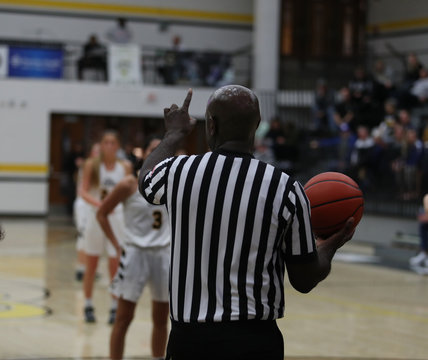 A basketball official signals one foul shot