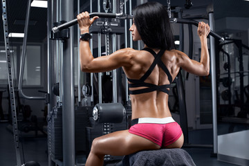 Fitness woman working out in gym doing exercise for back. Athletic girl doing lat pulldown