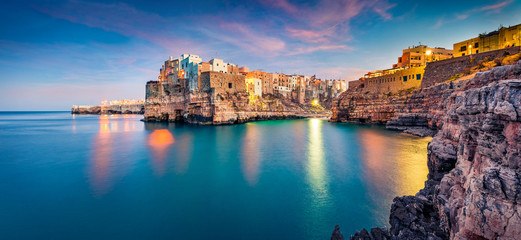 Panoramic evening cityscape of Polignano a Mare town, Puglia region, Italy, Europe. Amazing  spring sunrise view of Adriatic sea. Traveling concept background. Fotomurales