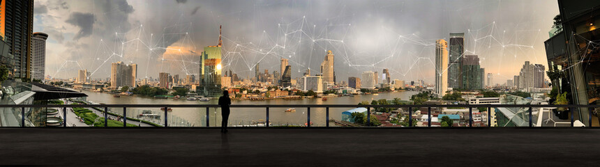 Wall Mural - Businessman standing using smart phone in modern space watching city night view.Business Wireless network and Connection technology concept.