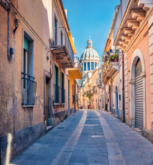 Bright spring cityscape of Ragusa town with  Duomo San Giorgio - baroque Catholic church on background. Nice morning scene of Sicily, Italy, Europe. Traveling concept background.