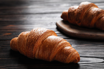 Tuinposter Brood Tasty fresh crispy croissants on wooden table