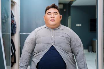 Fat Asian man wearing tight unbuttoned shirt