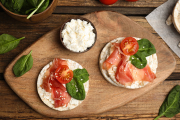 Puffed rice cakes with prosciutto, tomato and basil on wooden table, flat lay