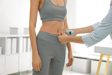 Nutritionist measuring woman's fat layer with caliper indoors, closeup