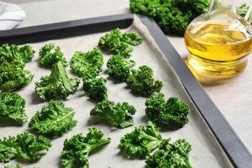 Raw cabbage leaves on baking sheet, closeup. Preparing kale chips