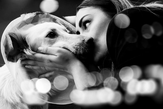 Beautiful impactful picture of a woman kissing her dog on the cheeks, black and white animal portrait