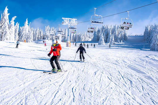 People enjoying skiing and snowboarding in mountain ski resort with beautiful winter landscape in the background