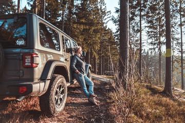 Frau mit Geländewagen im Wald in der Natur Fototapete