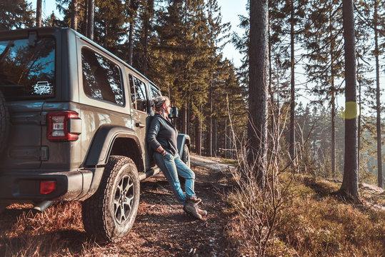 Frau mit Geländewagen im Wald in der Natur