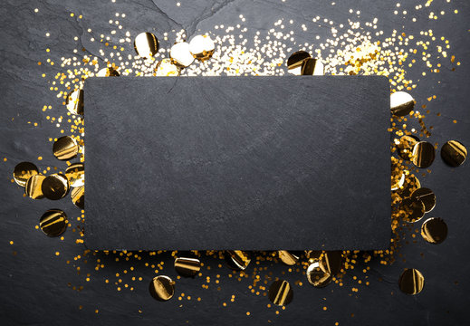 Slate board and confetti on black background, top view. Space for text