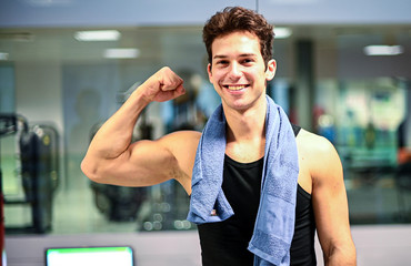 Smiling personal trainer in the gym showing his biceps