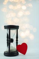 Fototapeta klepsydra oraz czerwone serce na tle światełek obraz