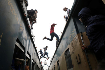 People jump between trains, who has come to attend at the final prayer of Bishwa Ijtema, which is considered the world's second-largest Muslim gathering after Haj, in Tongi