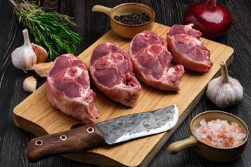 Chopped fresh lamb shank steak on cutting board with spice