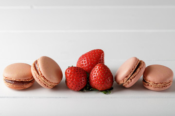 French macarons with strawberry on white wooden background