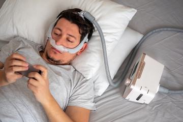 Healthy young man wearing under the nose nasal mask and using CPAP machine for sleeping smoothly and playing with his smart phone before sleeping. selective focus.