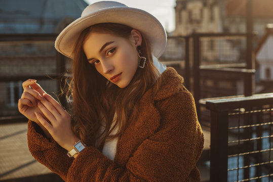 Outdoor fashion portrait of young elegant fashionable brunette woman, model wearing stylish white hat, wrist watch,  brown faux fur coat, posing at sunset, in European city. Copy empty space for text