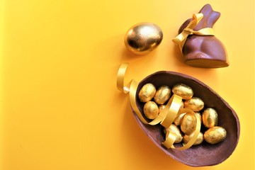 Golden chocolate Easter eggs and chocolate bunny with copy space