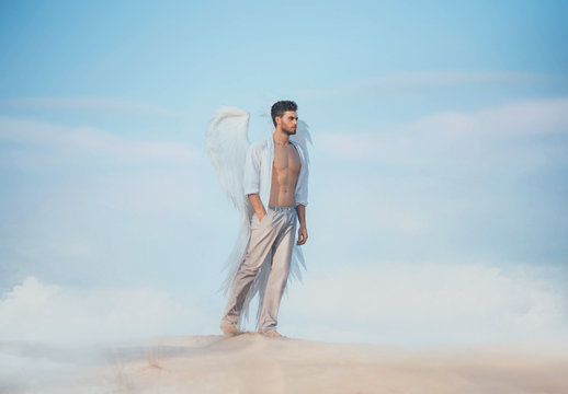 Handsome athletic man as an fallen angel walks sand desert blue sky cloud. Muscular sexy body naked torso beautiful body white shirt pants huge strong wings. fantasy design Creative costume clothes.