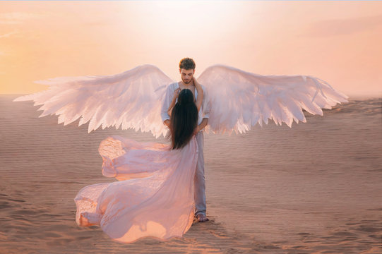 Men angel hugs young woman. Long dark hair dress silk fabric flying flutter wind. costume huge white wings. Bright color peach pink yellow sunset desert. Shoot back rear view turned away without face