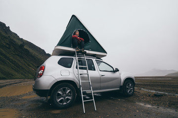 Landmannalaugar, Iceland - August 2018: Young woman sitting on a ladder next to offroad car with tent on the roof Wall mural