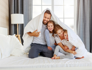 happy family mother, father and children laughing, playing and smiling in bed   at home.