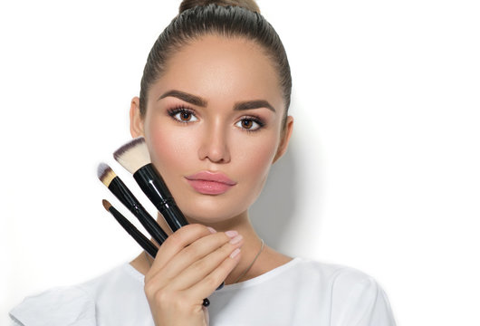 Beauty model girl, makeup artist holding set of make up brushes and smiling. Beautiful brunette young woman with perfect skin and nude make-up. Perfect skin closeup. Face contouring makeup. On white