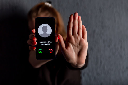 Phone call from unknown number. Scam, fraud or phishing with smartphone concept. Prank caller, scammer or stranger. Woman answering to incoming call. Hoax person with fake identity