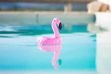 Foto op Canvas Flamingo Inflatable flamingo toy gently floats across swimming pool with scenic mountain background