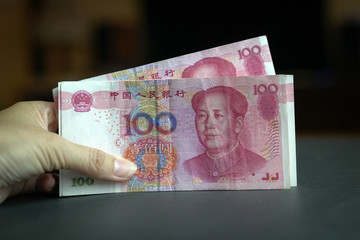 Hand holding a pile of 100 Chinese yuan bank notes