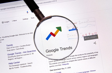 Outils Google pour entreprises Google Trends web site and logo under magnifying glass