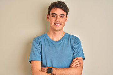 Teenager boy wearing casual t-shirt standing over isolated background happy face smiling with crossed arms looking at the camera. Positive person.