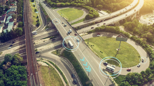 Autonomous Self Driving Cars Concept. Aerial view of cars and buses moving on city intersection and Artificial Intelligence scans road with sensors and control vehicles in traffic. Future
