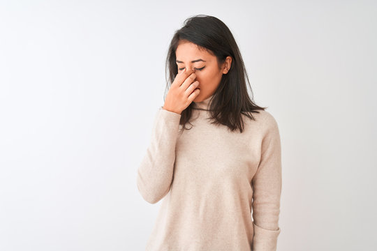 Beautiful chinese woman wearing turtleneck sweater standing over isolated white background tired rubbing nose and eyes feeling fatigue and headache. Stress and frustration concept.