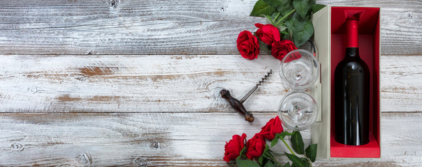 Happy Valentines Day celebration with red roses and a bottle of wine on white weathered wooden...