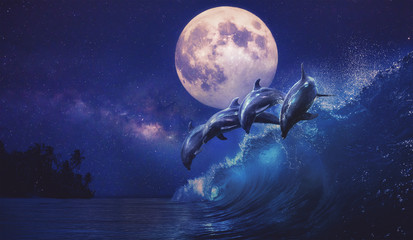 Beautiful night ocean with playful dolphins leaping on surfing wave and full moon on tropical background