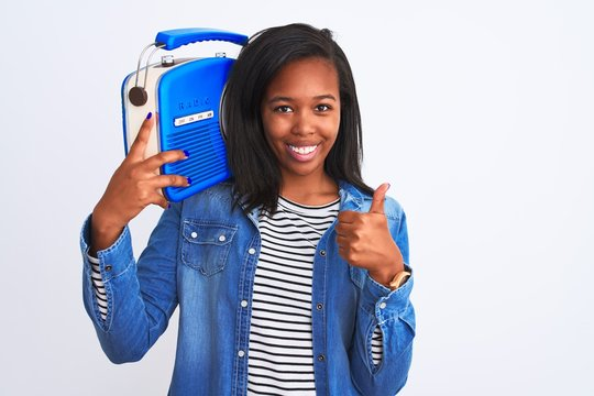 Young african american woman holding vintage retro radio over isolated background happy with big smile doing ok sign, thumb up with fingers, excellent sign