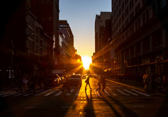 Fotomurales - Crowds of people walk through the busy intersection at 23rd Street and Fifth Avenue in New York City with the bright light of sunset