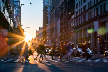 Fotomurales - Rays of sunset shine on the diverse crowds of people walking through a busy intersection in New York City