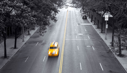 Fotomurales - Yellow taxi speeding down 42nd Street through a black and white Midtown Manhattan cityscape in New York City