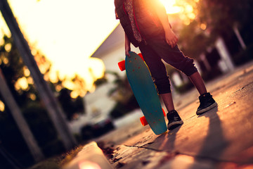 Image of little girl play skateboard in  late  summer or autumn.Preteen girl stand at the street with her green skateboard.Evening rim light shining through the scene.Concept of preteen activities.
